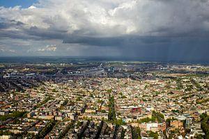 Een regenbui hangt boven de grachtengordel van Amsterdam van