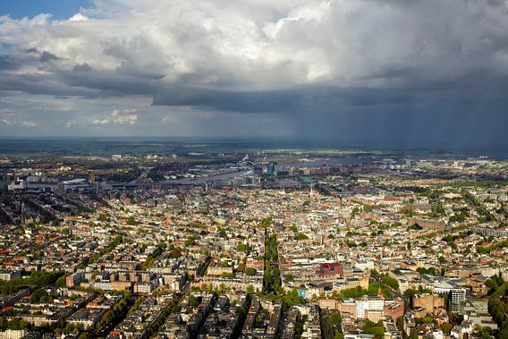 Een regenbui hangt boven de grachtengordel van Amsterdam