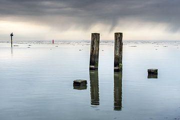 Het Wad bij Holwerd op een windstille dag en spiegelende palen. van