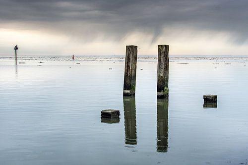 Het Wad bij Holwerd op een windstille dag en spiegelende palen. van Harrie Muis