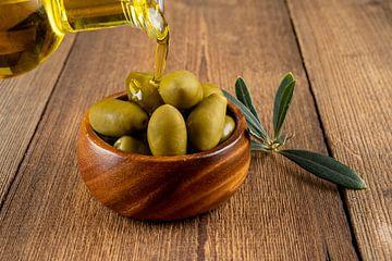 Olijfolie en groene olijven in houten kommetje van PhotoArt Thomas Klee
