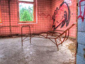 Rosa Zimmer mit rostigem Gestell einer Liege in einem alten, verlassenen Sanatorium