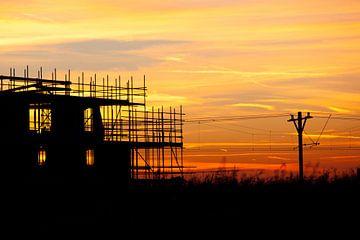 Zonsondergang bij de treinbaan met een silhouette gebouw in aanbouw van Dexter Reijsmeijer