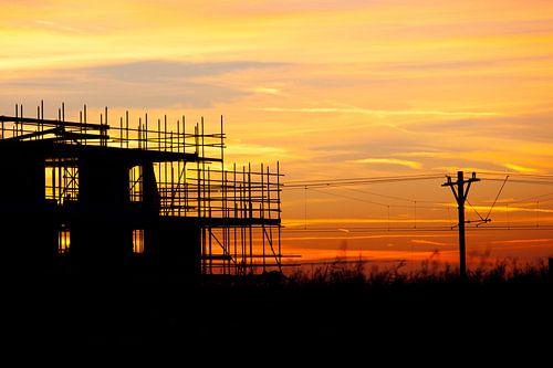 Zonsondergang bij de treinbaan met een silhouette gebouw in aanbouw