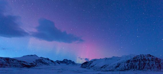 """Deze foto is in IJsland gemaakt op een heldere avond tijdens het zogenaamde """"blauwe uur"""". Dit is een moment na zonsondergang waardoor de lucht nog net een blauwe gloed geeft. Ook al was die avond de kans op noorderlicht zeer klein, het bleek toch de moeite waard te zijn om de kou te trotseren en zo tot dit resultaat te komen! En genot om naar te kijken!"""
