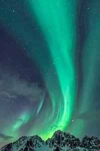 Aurores boréales s'élevant des sommets enneigés des Lofoten au nord de la Norvège