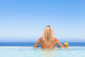 Vrouw  geniet van een drankje in het zwembad