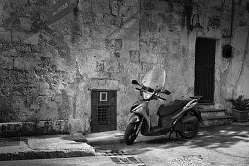 Scooter voor een rustieke muur in een stad in Italië in zwart-wit van iPics Photography