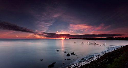 Visnetten in de Waddenzee bij zonsopkomst van