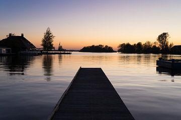 Een pier over rustig water aan de oever van een meer met reflectie van de zonsondergang en silhouett van Leoniek van der Vliet