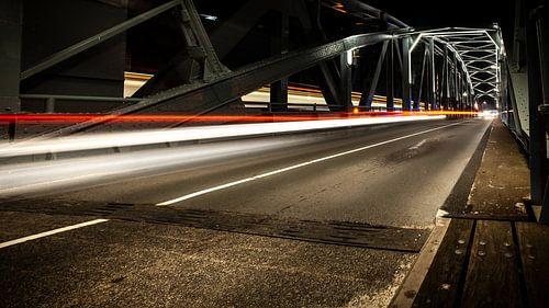Industriële ijzeren brug met rijdende autolichten in de nacht