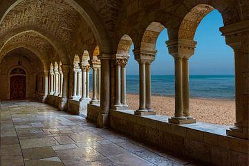 Zicht vanuit de gang van een oud klooster met oude stenen vloeren oude pilaren ,en een unieke doorki
