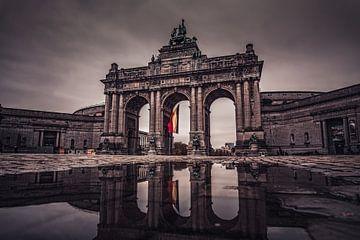 Die Triumphbögen des Cinquantenaire in Brüssel spiegeln sich in einer Wasserpfütze von Daan Duvillier