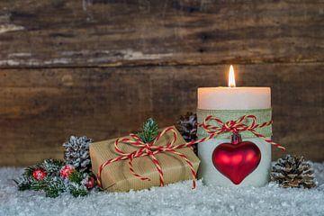 Kerstmiscompositie met brandende kaars en giftdoos op sneeuw van Alex Winter