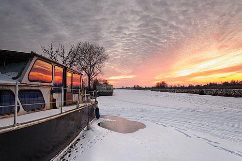 Boat in ice landscape at sunset van