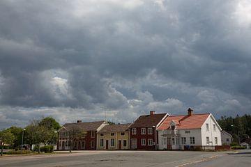 Donker lucht boven huisjes in dorp in zuid Zweden van Joost Adriaanse