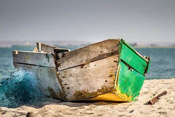 Oude houten vissersboot op het strand met visnet van Jan van Dasler