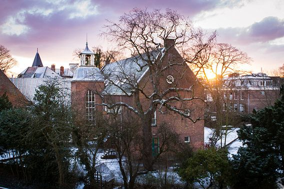 Zonsopkomst bij een besneeuwd Haarlem van Leon Weggelaar