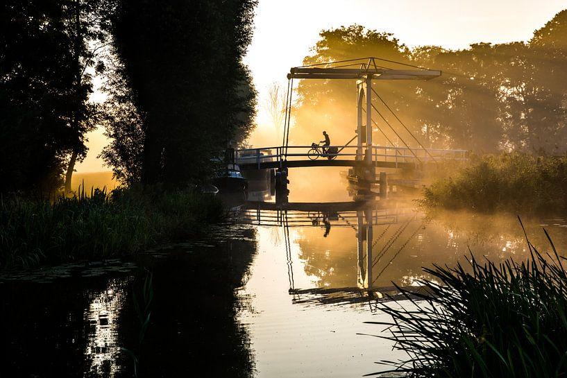 Eenzame krantenbezorger fietst over een brug in IJlst Friesland. One2expose Wout Kok Photography. van Wout Kok