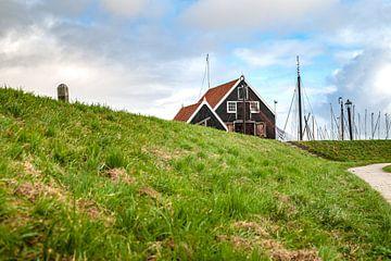 Hoge zee dijk met traditioneel vissers huisje aan de haven van