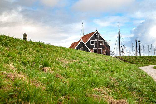 Hoge zee dijk met traditioneel vissers huisje aan de haven