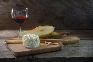 Roomblauwe stiltonkaas, portwijn, peer en wat knabbelstokken op een snijplank tegen een donkere rust van Maren Winter
