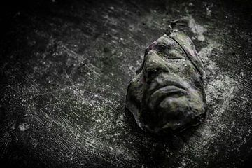 Een oud gebroken masker op een houten tafel von Steven Dijkshoorn