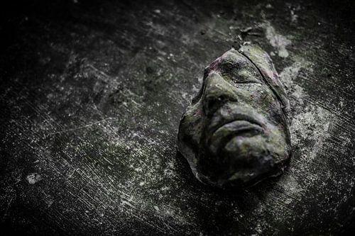 Een oud gebroken masker op een houten tafel