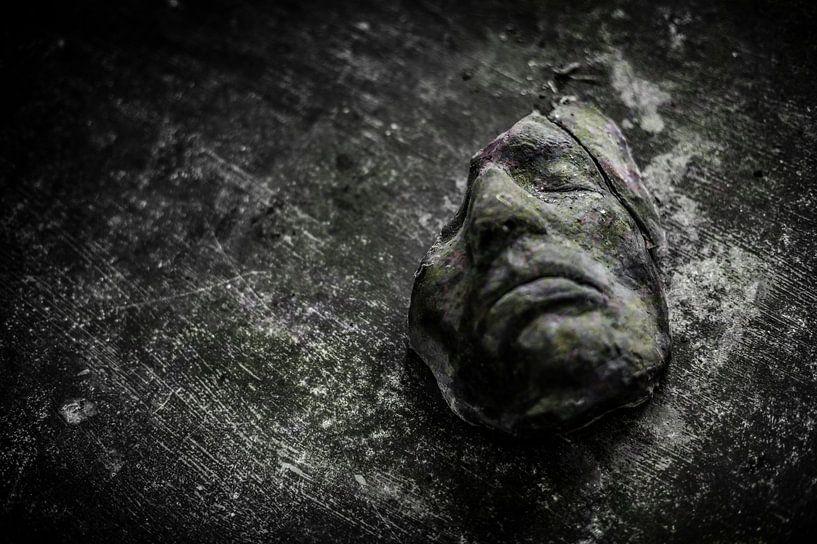 Een oud gebroken masker op een houten tafel sur Steven Dijkshoorn
