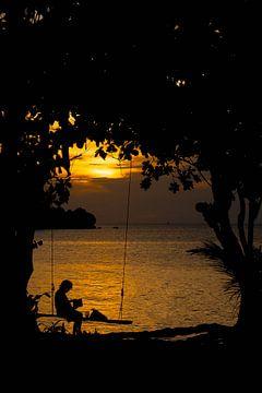 Vrouw op schommel bij zonsondergang van