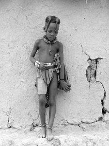 Himba kind tegen de muur van de hut. van