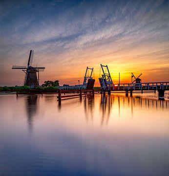 Windmolen en ophaalbrug bij zonsondergang van