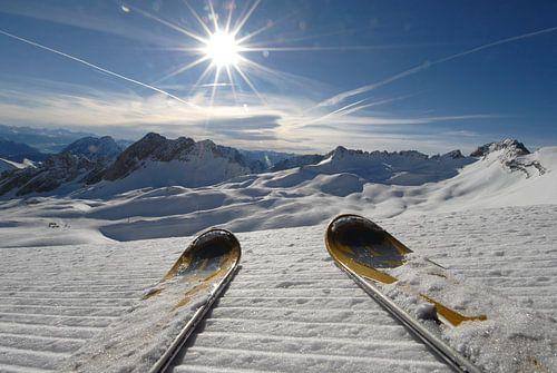 Ski's op sneeuw tussen de bergen en de felle zon er boven. Zugspitze, Europa