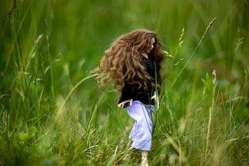 Jeune femme aux longs cheveux bruns dans les hautes herbes.