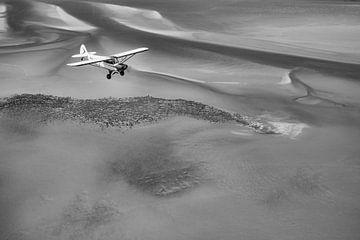 Vliegtuig boven de Waddenzee in zwart-wit van Planeblogger