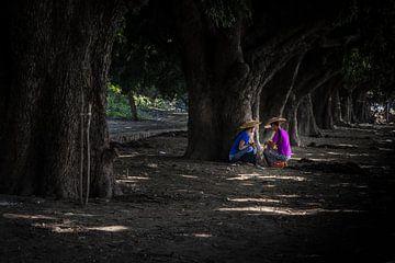 Twee vrouwen uit Myanmar zoeken de schaduw onder de bomen. Wout Kok One2expose Photography sur Wout Kok