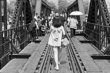 Vrouw loopt over brug in Kanchanaburi van Bart van Lier