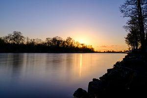 Ondergaande zon bij een meer. van Lidewij Olive
