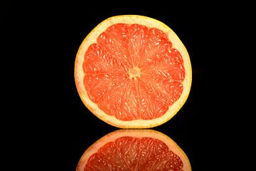 Dwarsdoorsnede een frisse oranje grapefruit op een zwarte achtergrond van Sjoerd van der Wal