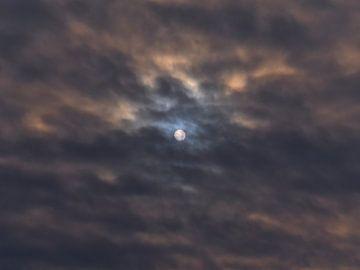 De zon schijnt door de oranje bewolkte lucht van Timon Schneider