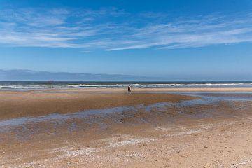 Noordzeestrand met eenzame wandelaar van Cilia Brandts