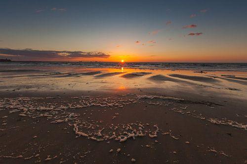Zonsondergang op het strand. van