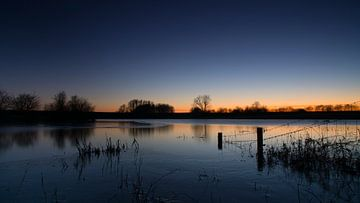 Half bevroren plas bij hoogwater na zonsondergang. van