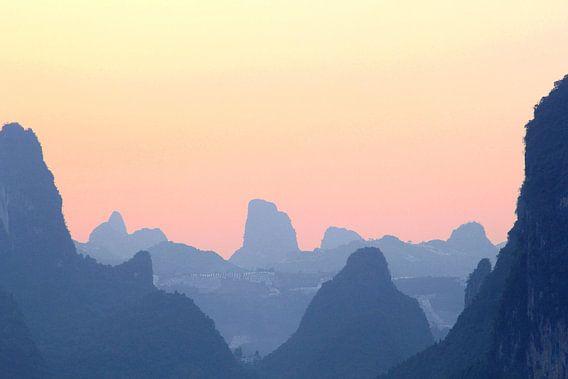 Landschap karstbergen nevel zonsondergang, China van  Inge Hogenbijl