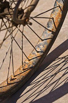 zonbeschenen verroeste fietswiel met een grafische schaduw van Tony Vingerhoets