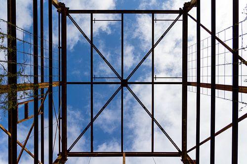 Urbex symmetrie - verroeste metalen constructie tegen een blauwe lucht met wolken