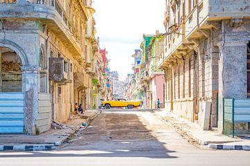Oldtimer Cubaanse auto rijdt door een kleurrijke zijstraat in Havana Cuba van Michiel Ton