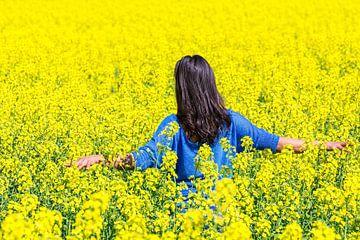 Die junge kolumbianische Frau steht in einem Feld mit gelbem Rapssamen von Ben Schonewille