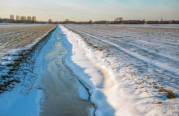 Bevroren sloot in besneeuwd Nederlands landschap van Ruud Morijn