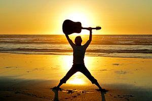 Gitaar muzikant op het strand met zonsondergang van